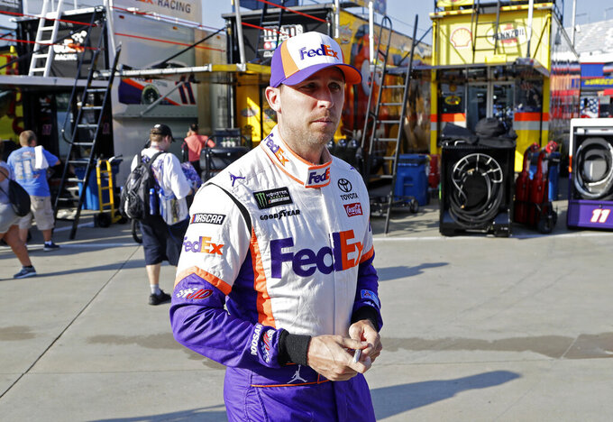 Denny Hamlin walks to his car before practice for Sunday's NASCAR Cup Series auto race at Charlotte Motor Speedway in Concord, N.C., Saturday, May 25, 2019. (AP Photo/Chuck Burton)