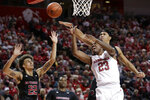 Rutgers' Ron Harper Jr., right rear, blocks a shot by Nebraska's Jervay Green (23) during the first half of an NCAA college basketball game in Lincoln, Neb., Friday, Jan. 3, 2020. At left is Rutgers' Caleb McConnell. (AP Photo/Nati Harnik)