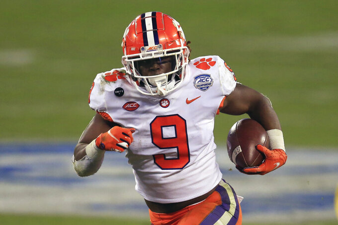 FILE - In this Saturday, Dec. 19, 2020 file photo, Clemson running back Travis Etienne (9) runs for a touchdown during the first half of the Atlantic Coast Conference championship NCAA college football game against Notre Dame in Charlotte, N.C. Brandon Beane didn't entirely rule out the possibility of adding a running back in the first two rounds, with Clemson's Travis Etienne and Alabama's Najee Harris rated as the top prospects.(AP Photo/Brian Blanco, File)