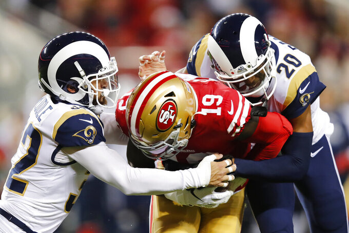 San Francisco 49ers wide receiver Deebo Samuel (19) is tackled by Los Angeles Rams free safety Eric Weddle, left, and cornerback Jalen Ramsey (20) during the first half of an NFL football game in Santa Clara, Calif., Saturday, Dec. 21, 2019. (AP Photo/John Hefti)