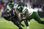 Baltimore Ravens defensive back Chuck Clark (36) is brought down by New York Jets center Jonotthan Harrison (78) and offensive tackle Brandon Shell (72) after he intercepted a pass from Jets quarterback Sam Darnold, not visible, prior to an NFL football game, Thursday, Dec. 12, 2019, in Baltimore. (AP Photo/Nick Wass)