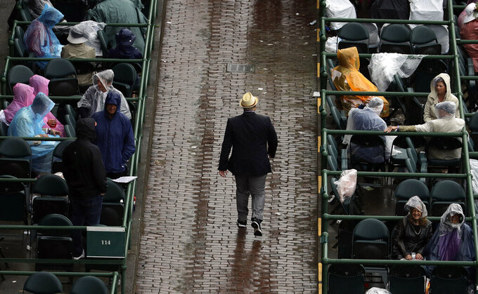 Fans wait in the rain before the 145th running of the Kentucky Derby horse race at Churchill Downs Saturday, May 4, 2019, in Louisville, Ky. (AP Photo/Charlie Riedel)