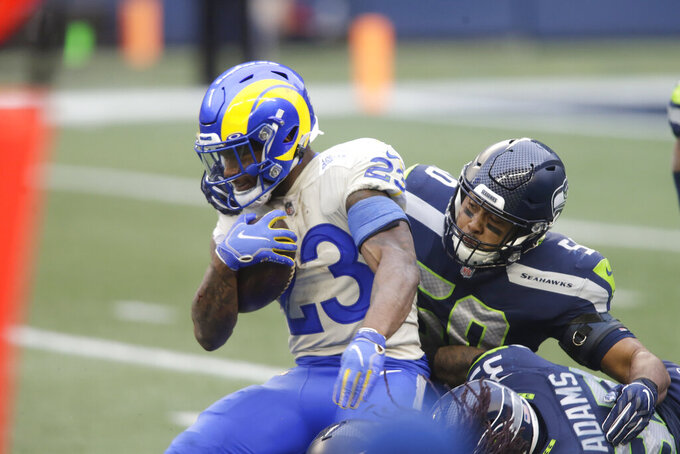 Los Angeles Rams running back Cam Akers (23) is brought down on a carry by Seattle Seahawks outside linebacker K.J. Wright during the first half of an NFL wild-card playoff football game, Saturday, Jan. 9, 2021, in Seattle. (AP Photo/Scott Eklund)