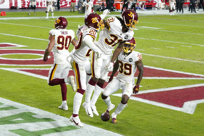 Washington Football Team strong safety Kamren Curl (31) celebrates his interception for a touchdown against the San Francisco 49ers with cornerback Jimmy Moreland (20), and defensive back Jeremy Reaves (39) during the second half of an NFL football game, Sunday, Dec. 13, 2020, in Glendale, Ariz. (AP Photo/Ross D. Franklin)