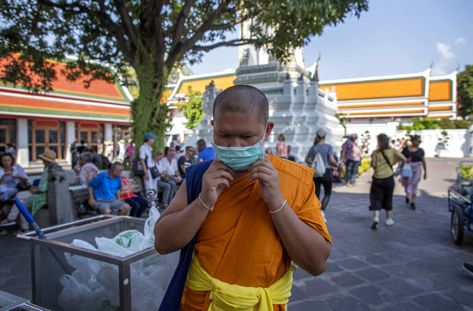 In this Feb. 13, 2020, photo, a Buddhist monk adjusts his face mask at the Wat Pho in Bangkok, Thailand. There were less crowds in Bangkok's popular Wat Pho, a centuries-old Buddhist temple known for its giant reclining buddha, due to the virus scare. The complex of temples is normally visited by thousands of tourists. (AP Photo/Gemunu Amarasinghe)