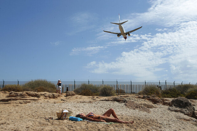A woman sunbathes on the beach as an airplane lands at the Balearic Islands capital of Palma de Mallorca, Spain, Wednesday, July 29, 2020. Concerns over a new wave of coronavirus infections brought on by returning vacationers are wreaking havoc across Spain's tourism industry, particularly in the Balearic Islands following Britain's effective ban on travel to the country. (AP Photo/Joan Mateu