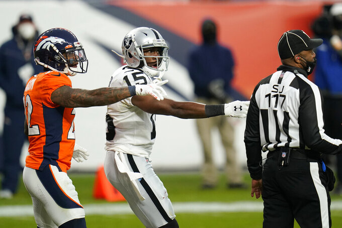 Denver Broncos strong safety Kareem Jackson (22) and Las Vegas Raiders wide receiver Nelson Agholor (15) react after a play during the first half of an NFL football game, Sunday, Jan. 3, 2021, in Denver. (AP Photo/Jack Dempsey)