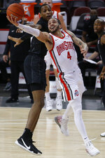 Ohio State's Duane Washington, right, shoots past Michigan State's Marcus Bingham during the first half of an NCAA college basketball game Sunday, Jan. 31, 2021, in Columbus, Ohio. (AP Photo/Jay LaPrete)