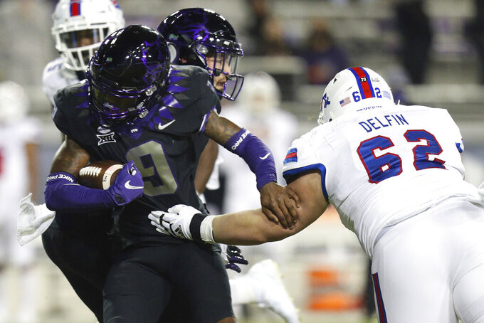 TCU cornerback C.J. Ceasar II (9) evades Louisiana Tech offensive lineman Abraham Delfin (62) after an interception in the first half during an NCAA college football game, Saturday, Dec. 12, 2020. (AP Photo/ Richard W. Rodriguez)
