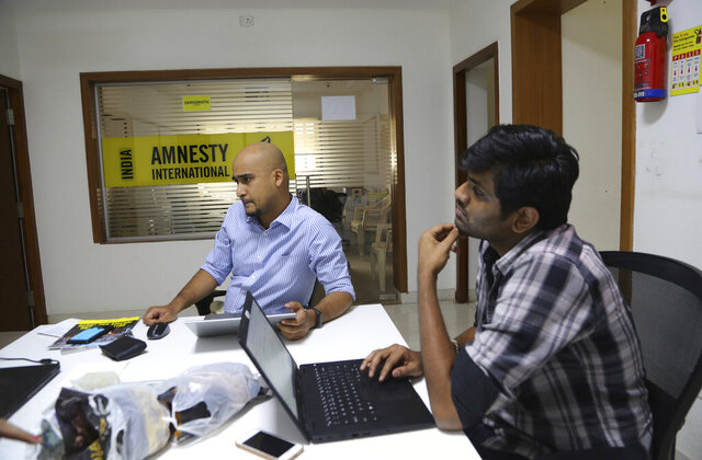 FILE - In this Tuesday, Feb. 5, 2019, file photo, Amnesty International India employees work at their headquarters in Bangalore, India. The Human rights watchdog said on Tuesday, Sept. 29, 2020, that it was halting its operation in India, citing reprisals from the government and the freezing of its bank accounts. Its announcement comes at a time amid growing concerns over the state of free speech in India where critics accuse Prime Minister Narendra Modi and his Hindu nationalist government of increasingly brandishing laws to silence human rights activists, intellectuals, filmmakers, students and journalists. (AP Photo/Aijaz Rahi, File)