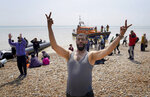 A man gestures as people thought to be migrants stand on the beach after arriving on a small boat at Dungeness in Kent, England, Monday July 19, 2021. They were later taken away by Border Force staff. (Gareth Fuller/PA via AP)