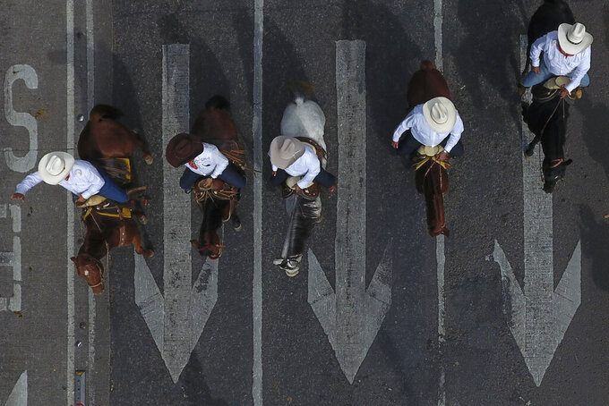 In this Wednesday, Nov. 20, 2019 photo, men ride horses down Paseo de la Reforma during a parade marking the 109th anniversary of the start of the Mexican Revolution, in Mexico City. More than 1,000 participants dressed in period clothing rode through the streets of the capital after reenacting scenes from the revolution in the city's main square. (AP Photo/Rebecca Blackwell)