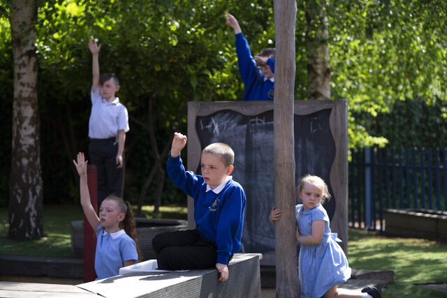 Children at Seymour Road Academy take part in a Commando Joe's character education program run by former soldier Mike Hamilton during the coronavirus outbreak in Manchester, England, Wednesday May 20, 2020. Hula hoops, camouflage mats and tires aren't typical supplies needed during the coronavirus pandemic. But they're useful props as British veteran Mike Hamilton prepares to lead children in a military-style game designed to boost their resilience and mental health at a time of atypical stress. (AP Photo/Jon Super)