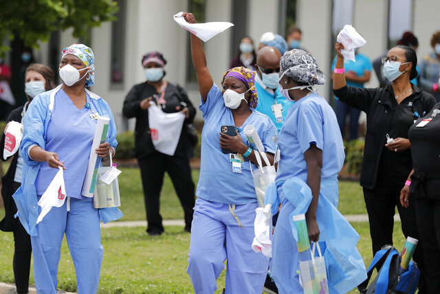 FILE - In this May 15, 2020, file photo, healthcare workers at New Orleans East Hospital wave handkerchiefs and dance to a jazz serenade, as a tribute for their care for COVID-19 patients, by the New Orleans Jazz Orchestra, outside the hospital in New Orleans. An act of generosity or self-sacrifice. A whimsical gesture to distract neighbors from anxiety or cabin fever. A helping hand to a person thrown out of a job, support for a patient struggling with COVID-19, solidarity with the medical professional toiling day and night to save them. Nearly three months later, there's been no end to the tales of good deeds we've found. (AP Photo/Gerald Herbert, File)