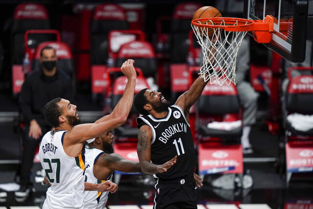 Brooklyn Nets' Kyrie Irving (11) drives past Utah Jazz's Rudy Gobert (27) during the first half of an NBA basketball game Tuesday, Jan. 5, 2021, in New York. (AP Photo/Frank Franklin II)