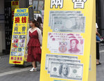 A woman passes by signs for a money exchange at a shopping district in Seoul, South Korea, Thursday, July 18, 2019. South Korea's central bank on Thursday cut its policy rate for the first time in three years to shore up growth threatened by a trade dispute with Japan. (AP Photo/Ahn Young-joon)