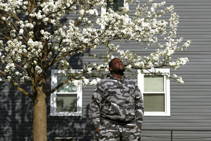 Nikko Ross stands for a portrait at his home, Thursday, April 15, 2021, in Evanston, Ill. Acknowledging past racist policies, Evanston is giving eligible Black residents $25,000 housing grants for down payments, repairs or existing mortgages this year. He'll seek a grant, either for his down payment, or for his mother to repair her six-bedroom house. (AP Photo/Shafkat Anowar)
