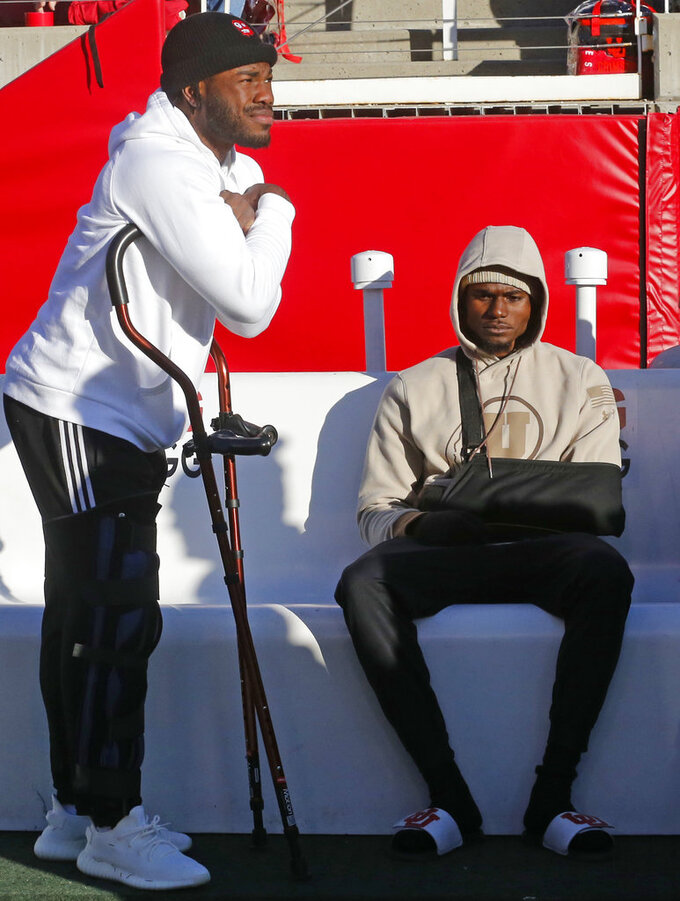 Injured Utah's running back Zack Moss, left, and quarterback Tyler Huntley, right, look on before the start of their NCAA college football game against Oregon Saturday Nov. 10, 2018, in Salt Lake City. (AP Photo/Rick Bowmer)
