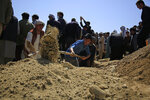 Afghan men bury a victim of deadly bombings on Saturday near a school, at a cemetery west of Kabul, Afghanistan, Sunday, May 9, 2021. The Interior Ministry said Sunday the death toll in the horrific bombing at the entrance to a girls' school in the Afghan capital has soared to some 50 people, many of them pupils between 11 and 15 years old, and the number of wounded in Saturday's attack has also climbed to more than 100. (AP Photo/Mariam Zuhaib)