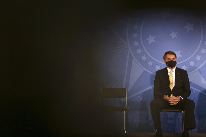 FILE - In this May 15, 2020, file photo, Brazil's President Jair Bolsonaro wears a mask amid the COVID-19 pandemic during an event at Planalto presidential palace in Brasilia, Brazil. Bolsonaro said Tuesday, July 7, he tested positive for COVID-19 after months of downplaying the virus's severity while deaths mounted rapidly inside the country. (AP Photo/Eraldo Peres, File)