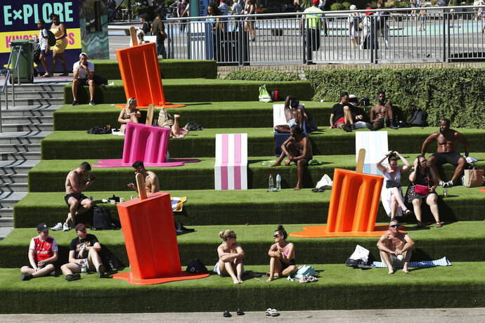 People sunbathe on the steps near Granary Square, King's Cross, as the warm weather continues, in London, Friday, Aug. 7, 2020. The UK could see record-breaking temperatures with forecasters predicting Friday could be the hottest day of the year. (Jonathan Brady/PA via AP)
