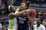 FILE - This Feb.16, 2020, file photo shows South Florida's Shae Leverett, left, and Connecticut's Olivia Nelson-Ododa during the first half of an NCAA college basketball game in Tampa, Fla. UConn, one of the original members of the Big East Conference, is hoping a return to the league will help put the Huskies back among the elite programs in college basketball. The Huskies spent seven years in the American Athletic Conference, on a mostly downward trajectory since winning a fourth national title in 2014. (AP Photo/Mike Carlson, File)