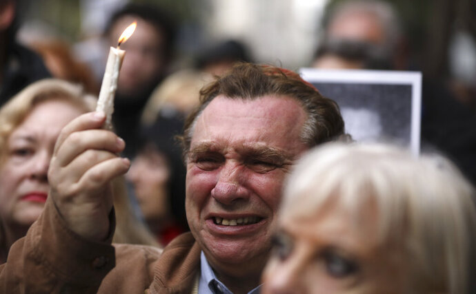 A man cries as he holds up a candle on the 25th anniversary of the bombing of the AMIA Jewish center that killed 85 people in Buenos Aires, Argentina, Thursday, July 18, 2019. (AP Photo/Natacha Pisarenko)