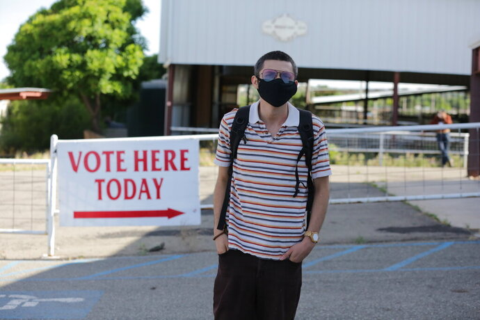 Bernie Sanders supporter Sergio Marquez poses for a photo outside of a polling station during primary voting on Tuesday, June 2, 2020, in Santa Fe, New Mexico. Marquez wanted to vote for Sanders even though he's out of the race and Joe Biden is the presumptive Democratic presidential nominee. But Marquez says he wasn't able to vote because he had not registered as a Democrat; New Mexico's primaries are closed to party members. (AP Photo/Cedar Attanasio)