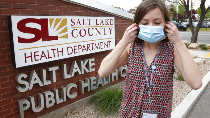 FILE - In this May 19, 2020, file photo, health investigator Mackenzie Bray adjusts her mask at the Salt Lake County Health Department in Salt Lake City. Contact tracers around Utah's capital of Salt Lake City have seen caseloads double and cooperation wane since government leaders reopened the economy, Bray said. (AP Phoo/Rick Bowmer, File)