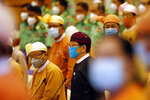 Lower House Speaker T Khun Myat, center, and other parliament members wearing face masks arrive for a parliament session, Monday, June 1, 2020, at the parliament building in Naypyitaw, Myanmar. (AP Photo/Aung Shine Oo)