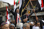 Druze men carry Sidqi al-Maqt, left, and Amal Abu Saleh as they wave Syrian flags upon their release from Israeli prison in the village of Majdal Shams on the border with Syria Friday, Jan. 10, 2020. (AP Photo/Ariel Schalit)