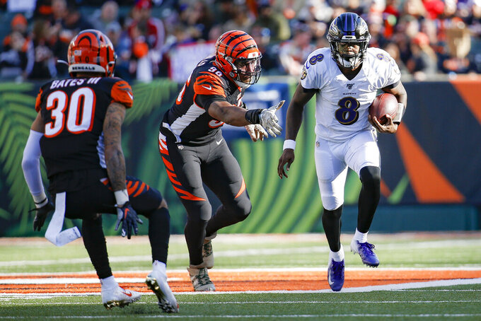Baltimore Ravens quarterback Lamar Jackson (8) runs the ball for a touchdown against Cincinnati Bengals defensive end Carlos Dunlap (96) during the second half of NFL football game, Sunday, Nov. 10, 2019, in Cincinnati. (AP Photo/Frank Victores)