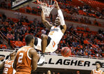 Oklahoma State's Cameron McGriff dunks in front of Texas' Matt Coleman III during the first half of an NCAA college basketball game Tuesday, Jan. 8, 2019, in Stillwater, Okla. (Evan Brown/Tulsa World via AP)