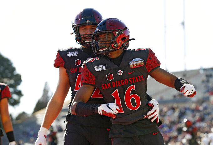 San Diego State cornerback Luq Barcoo (16) celebrates with linebacker Troy Cassidy (42) after an interception in the end zone during the first half of the New Mexico Bowl NCAA college football game against Central Michigan on Saturday, Dec. 21, 2019 in Albuquerque, N.M. (AP Photo/Andres Leighton)