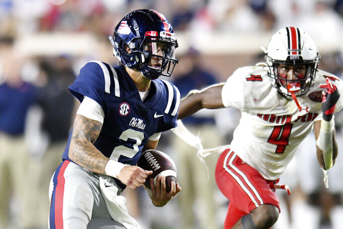 Mississippi quarterback Matt Corral (2) is chased by Austin Peay cornerback Koby Perry (4) during an NCAA college football game in Oxford, Miss., Saturday, Sept. 11, 2021. (AP Photo/Bruce Newman)
