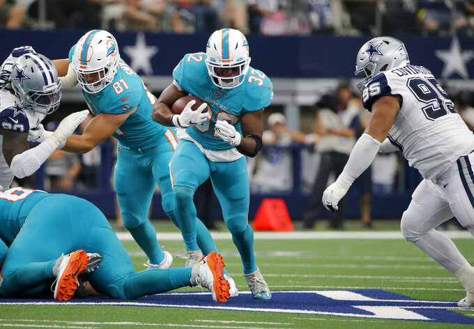 Miami Dolphins' Kenyan Drake (32) finds running room as Dallas Cowboys defensive end Christian Covington (95) pursues in the first half of an NFL football game in Arlington, Texas, Sunday, Sept. 22, 2019. (AP Photo/Michael Ainsworth)