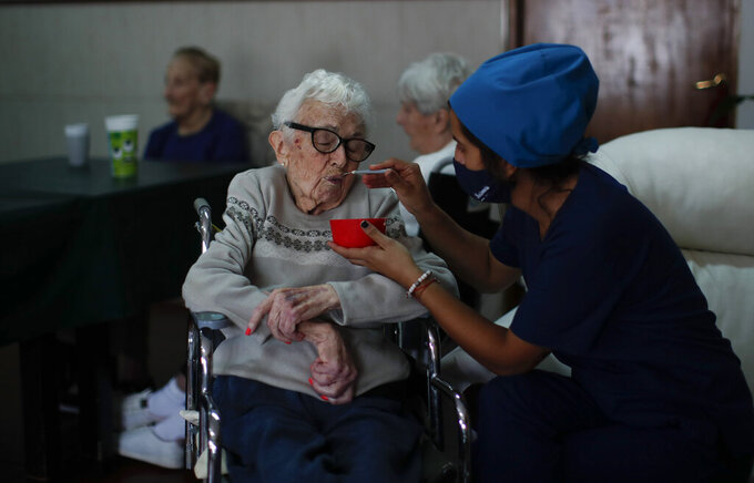 Nurse Rocio Lescano feeds Dora Amestoy her breakfast at the Reminiscencias residence for the elderly in Tandil, Argentina, Monday, April 5, 2021. Residents here do not have physical contact with their families or leave the residence due to the COVID-19 pandemic, but stay active with group activities within the facility. (AP Photo/Natacha Pisarenko)