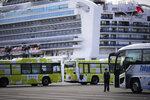 Buses are parked near the quarantined Diamond Princess cruise ship Wednesday, Feb. 19, 2020, in Yokohama, near Tokyo. Passengers tested negative for COVID-19 will start disembarking Wednesday. (AP Photo/Jae C. Hong)