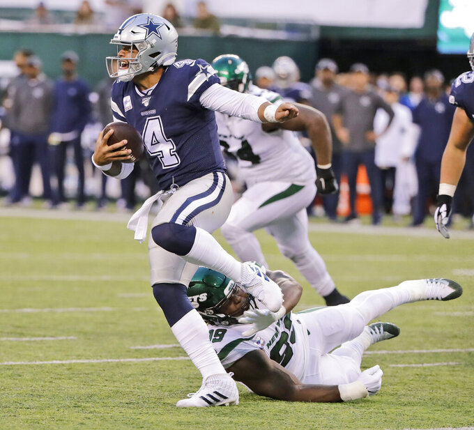 Dallas Cowboys quarterback Dak Prescott tries to outrun New York Jets defenders during the second half of an NFL football game, Sunday, Oct. 13, 2019, in East Rutherford, N.J. (AP Photo/Frank Franklin II)
