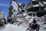 A man rides past destruction in the town of Douma, the site of a suspected chemical weapons attack, near Damascus, Syria, Monday, April 16, 2018. Faisal Mekdad, Syria's deputy foreign minister, said on Monday that his country is