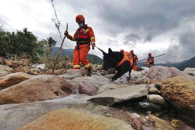 In this photo released by Xinhua News Agency, rescue workers and a rescue dog search for victims in the aftermath of flooding in Yihai Town of Mianning County in southwestern China's Sichuan Province on Sunday, June 28, 2020. Authorities in southwestern China's Sichuan province say some have died and others are missing following heavy rains, adding to a grow toll from summer flooding across the country. (Wang Yun/Xinhua via AP)