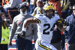 Michigan's Zach Charbonnet (24) runs down the sideline, past Illinois coach Lovie Smith, left, during the first half of an NCAA college football game Saturday, Oct. 12, 2019, in Champaign, Ill. (AP Photo/Holly Hart)