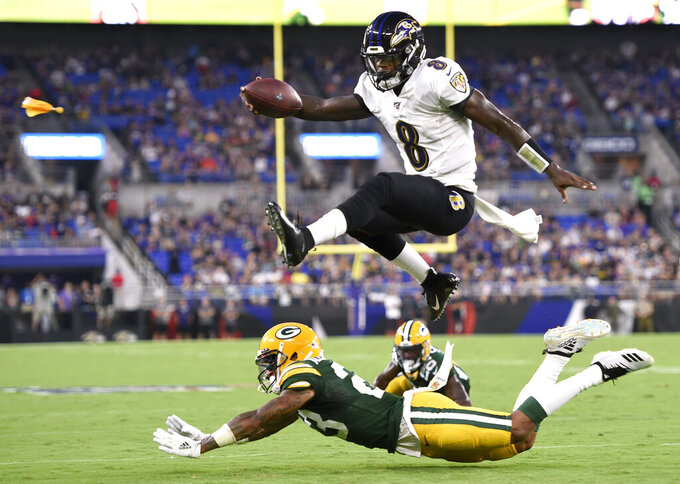 Baltimore Ravens quarterback Lamar Jackson (8) leaps over Green Bay Packers cornerback Jaire Alexander (23) during the first half of a NFL football preseason game, Aug. 15, 2019, in Baltimore. The play was called back on a penalty on the Ravens. (AP Photo/Gail Burton)