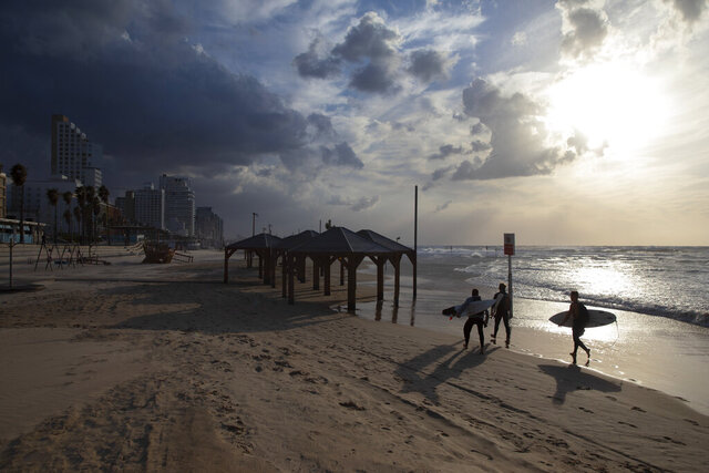 Surfers carry their boards along the beach front during a nationwide lockdown to curb the spread of the oronavirus, In Tel Aviv, Israel, Sunday, Jan. 17, 2021. (AP Photo/Oded Balilty)