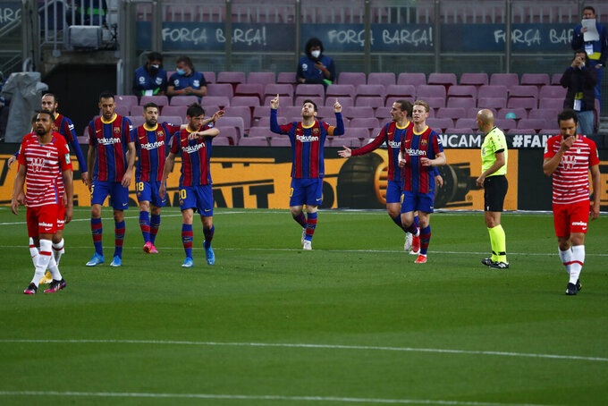 Barcelona's Lionel Messi, center, celebrates with his teammates after scoring his side's opening goal during the Spanish La Liga soccer match between FC Barcelona and Granada at the Camp Nou stadium in Barcelona, Spain, Thursday, April 29, 2021. (AP Photo/Joan Monfort)