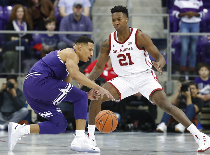 TCU guard Desmond Bane, left, tries to find a way past Oklahoma forward Kristian Doolittle (21) during the first half of an NCAA college basketball game in Fort Worth, Texas, Saturday, Feb. 16, 2019. (AP Photo/LM Otero)