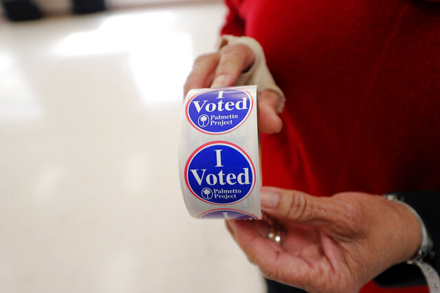 Polling manager Diana Belton shows a roll of voting stickers as people arrive to vote in the Democratic presidential primary in Hopkins, S.C., Saturday, Feb. 29, 2020. (AP Photo/Gerald Herbert)