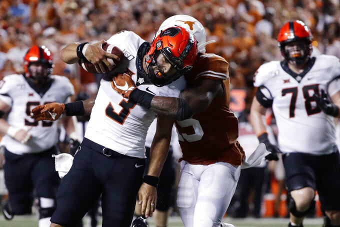 Oklahoma State quarterback Spencer Sanders (3) is hit by Texas defensive back Chris Brown (15) on a run during the second half of an NCAA college football game Saturday, Sept. 21, 2019, in Austin, Texas. (AP Photo/Eric Gay)
