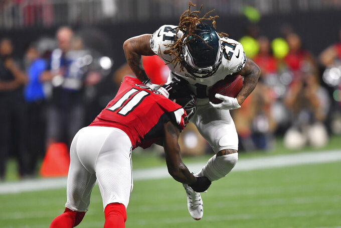 Atlanta Falcons wide receiver Julio Jones (11) makes the hit after Philadelphia Eagles cornerback Ronald Darby (21) made an interception during the second half of an NFL football game, Sunday, Sept. 15, 2019, in Atlanta. (AP Photo/John Amis)