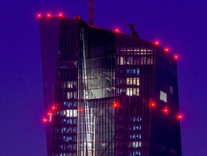 FILE - In this Tuesday, Sept. 7, 2021 file photo red lights shine on top of the European Central Bank in Frankfurt, Germany. The ECB will have a meeting of the governing council on Thursday. The European Central Bank's governing council meets Thursday, Sept. 9, 2021 to decide monetary policy for the 19 countries that use the euro. Analysts say the central bank may ease back on its support for the economy against a background of improving economic activity. (AP Photo/Michael Probst, file)
